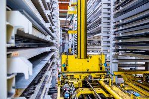 A yellow crane travels down an aisle of flat sheet storage