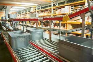 A series of conveyors transport grey totes around a mezzanine pick floor as part of a zone pick solution