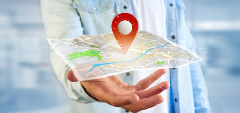 A pin indicates the location on a map which is hovering over the outstretched hand of a person in a blue shirt and white t-shirt