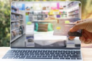 A hand holds a black credit card as they browse a homeware store online on a silver laptop with black keys