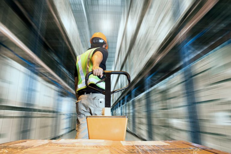 A warehouse operative pulls a pallet of product down a blurred warehouse aisle using a pump truck