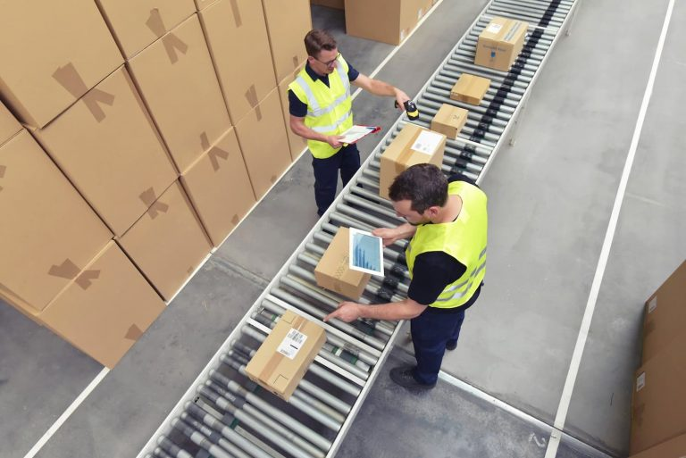 Two men in high vis jackets are scanning parcels on a conveyor in a warehouse as part of the intake, despatch or returns process