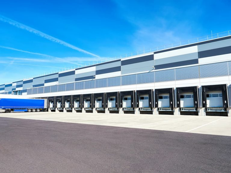 A warehouse exterior with many dock level doors and a parked trailer sits in the foreground against a bright blue sky in the background